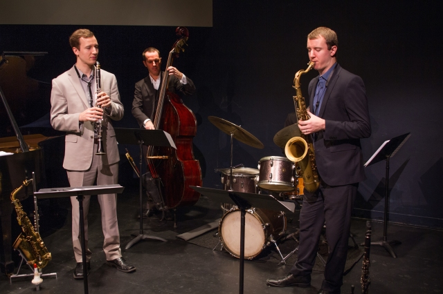 Clovis Nicolas on acoustic bass, Will Anderson (light suit) on alto sax, and Peter Anderson (dark suit) on tenor sax. Photo by Eileen O'Donnell